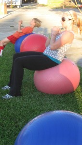 Tami is enjoying a ball workout outdoors, with trainer Rhonda Liebig.